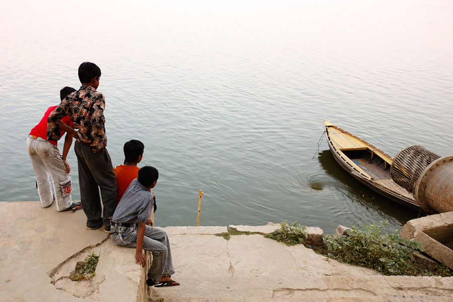 Boys watching the Ganges drain down a plug hole in Varanassi