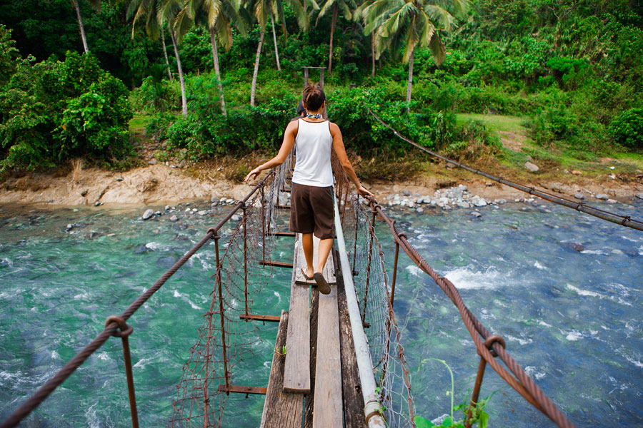 Monica crossing a hanging bridge near Adams, Laoag